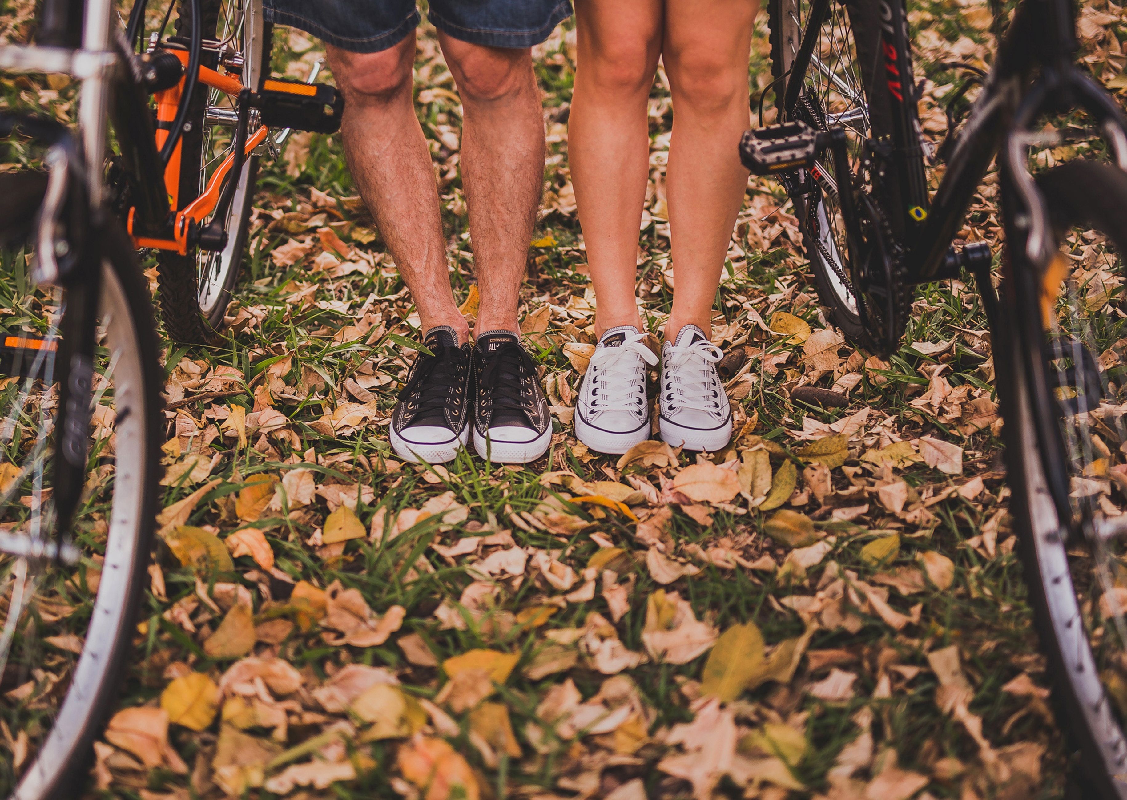 two bicycles and the legs and feet of a man and woman in sneakers