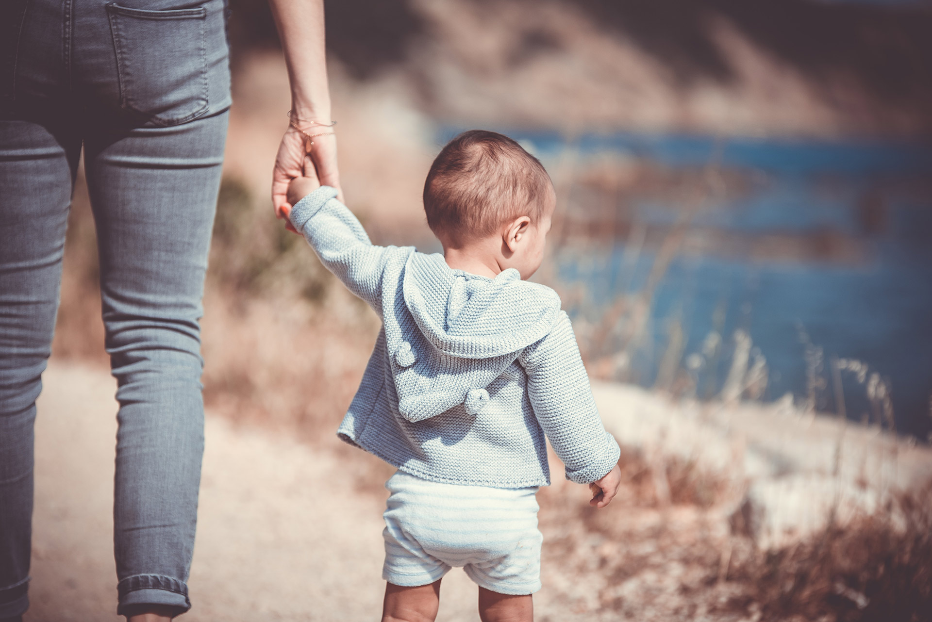 toddler in blue holding hand of adult woman in denim jeans