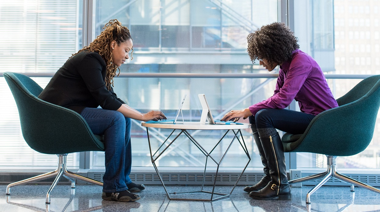 two women reviewing computers