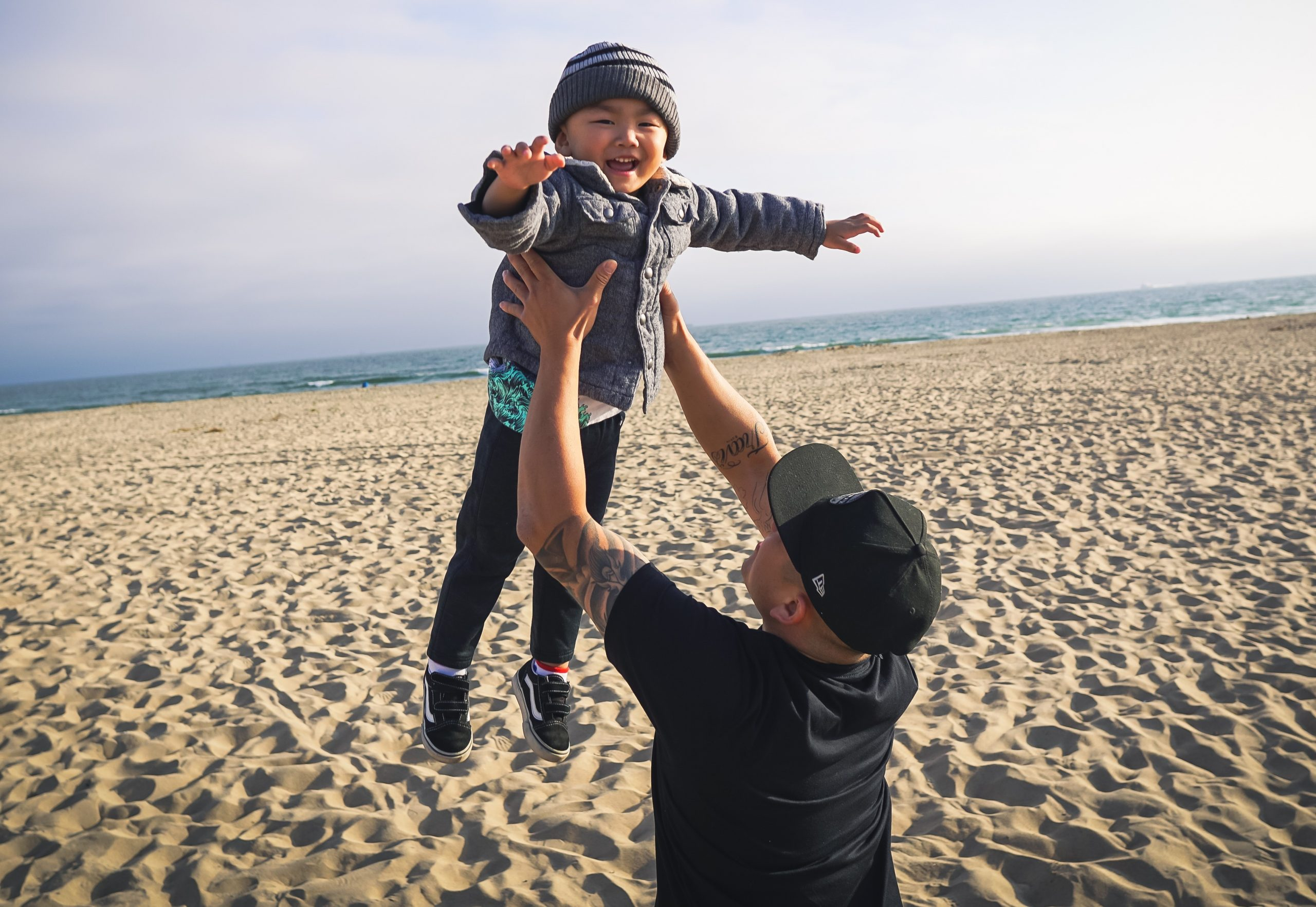 man on beach throwing toddler into the air playfully